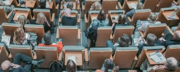 Image shows a lecture hall crowded with students