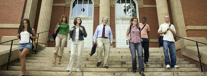 diverse students walking out of a campus building