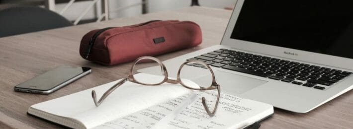 glasses on a notebook near a computer and cell phone