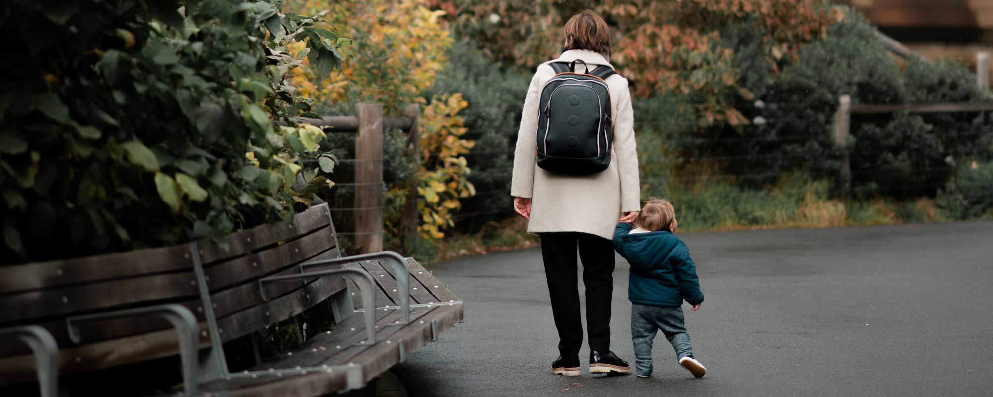 a mother walking with her toddler, she is wearing a backpack implying she is a student