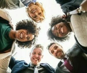 group of diverse students looking down at the camera and smiling. their heads form a circle