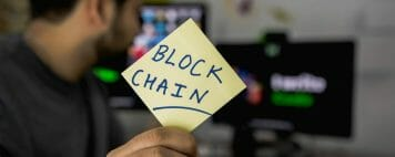"What is blockchain? An image of a man at a computer holding up a sign reading ""Blockchain"""