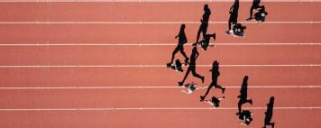 birds eye view of students running on a track in a V formation