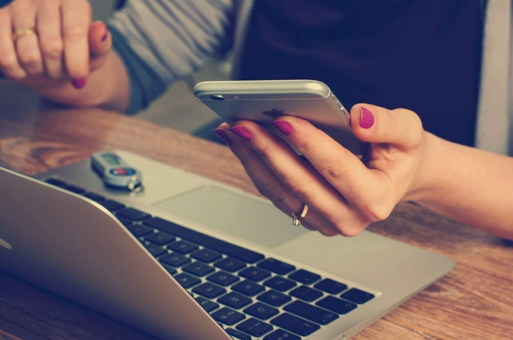Image of a student holding a phone, at a laptop