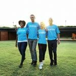 "Alumni volunteer engagement: Image of four alumni volunteers in blue ""volunteer"" shirts"