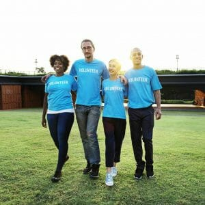 "Alumni volunteer engagement: Image of four alumni volunteers in blue ""volunteer"" shirts"
