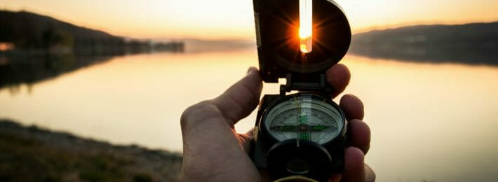 Higher Education Mergers - Image of a Compass at Sunset