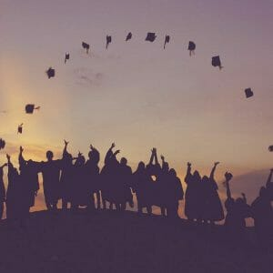 Students throwing graduation caps in an arch