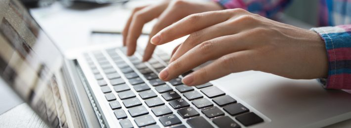 Cropped view of person's hands typing on laptop computer