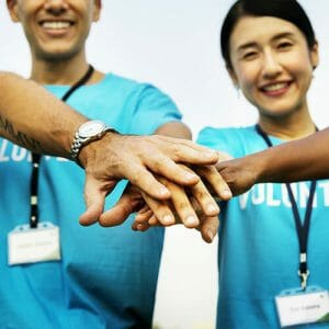 """Huddle up"" hands together image for volunteers"