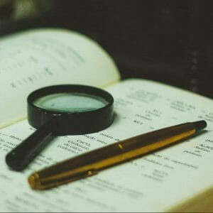 click pen and magnifying glass on book page
