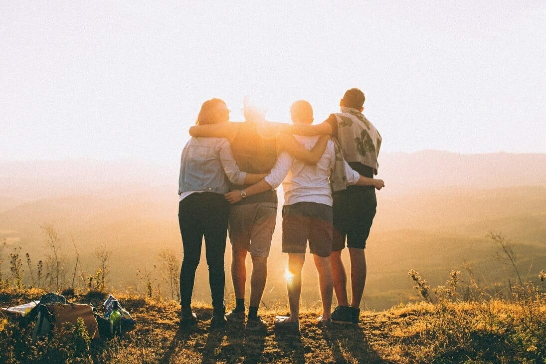 Developing Student Leaders - Image of Four Students Facing a Sunset Together