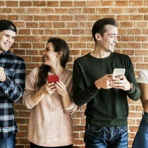 Happy friends using smartphones social media concept