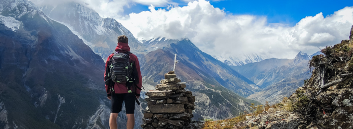 Photo of a person in the mountains gazing toward the future