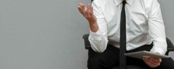 Displeased frustrated businessman in eyeglasses holding pc tablet
