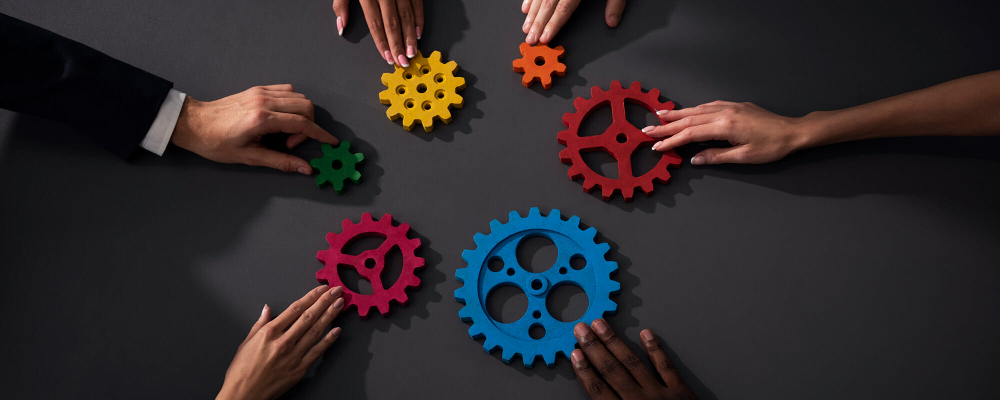 diverse group of individuals pushing colorful gears on a table to each other