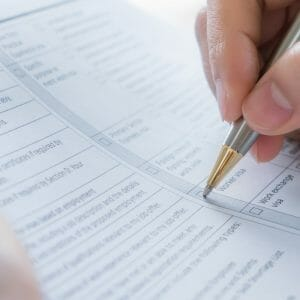 Close up of a female hand filling out an assessment form