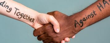 Handshake between black and white people standing together against hate