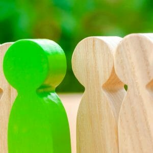 Green wooden figure standing out among other wooden figures