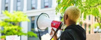 Person of color holding a megaphone at a peaceful protest