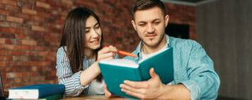 University students reading textbook together