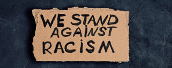 We stand against racism written on cardboard